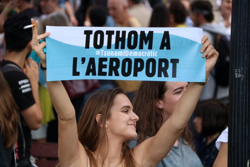 Una manifestant mostra un cartell de Tsunami Democràtic cridant a la gent a mobilitzar-se a l'aeroport. Imatge del 14 d'octubre de 2019.